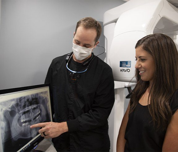 Dentist and dental patient reviewing dental x-rays