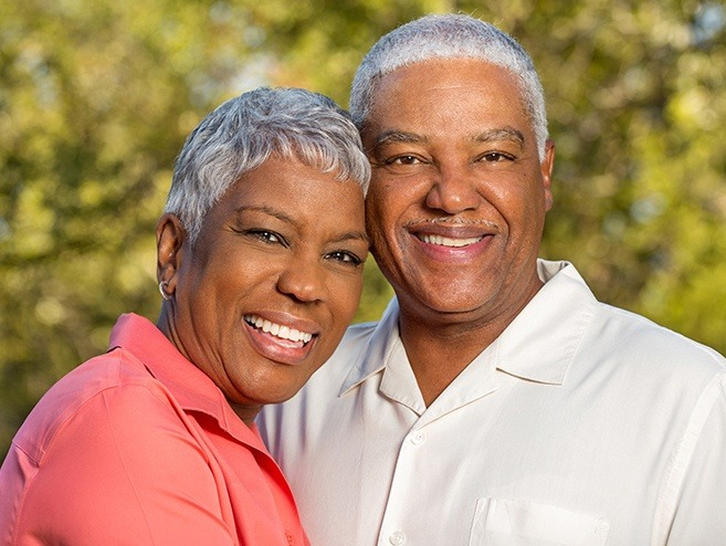 Man and woman smiling after dental bonding treatment