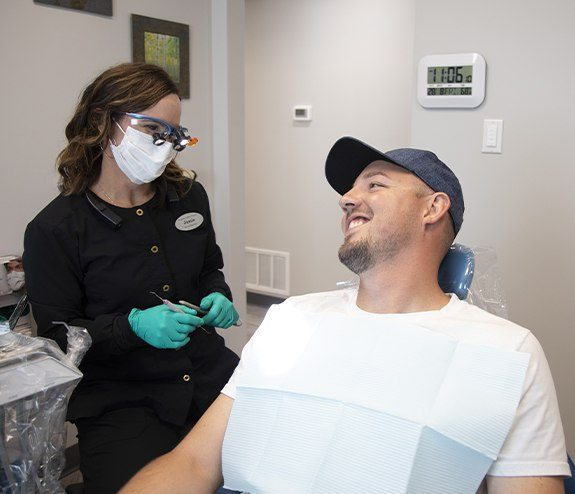 Man smiling at dental team member during dental bonding treatment