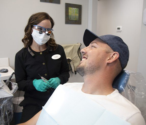 Man with dental implant replacement tooth smiling at dental team member