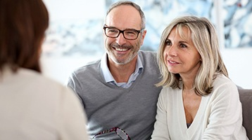 Smiling older couple speaking with an implant dentist in Longmont