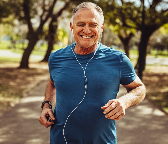 An older man with dental implants in Longmont jogging