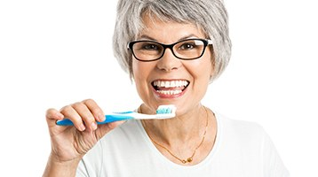 Older woman with dental implants in Longmont holding a toothbrush