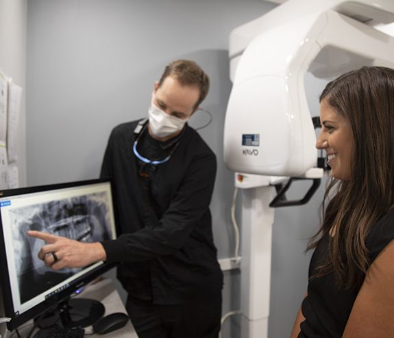 Dentist pointing to dental x-rays talking to patient