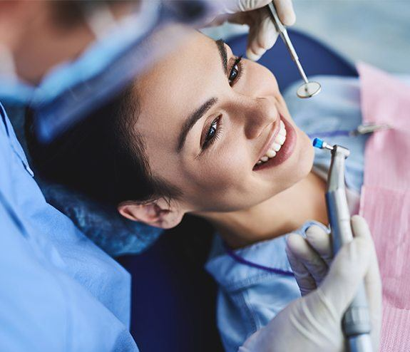 Woman smiling during dental checkup and teeth cleaning visit