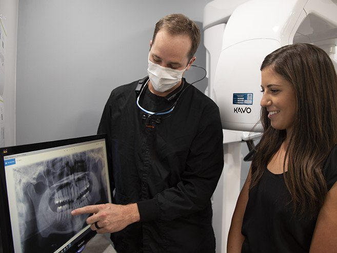 Dentist and patient reviewing x-rays during restorative dentistry