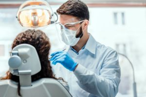 a patient visiting their dentist in Longmont, who is wearing a mask and face shield