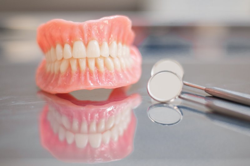 Full dentures next to a dental mirror