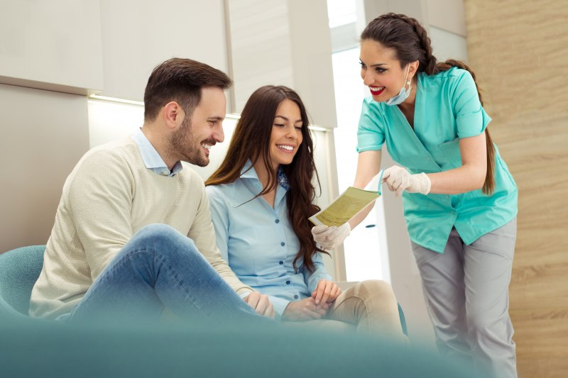 Dentist reviewing paperwork with patients